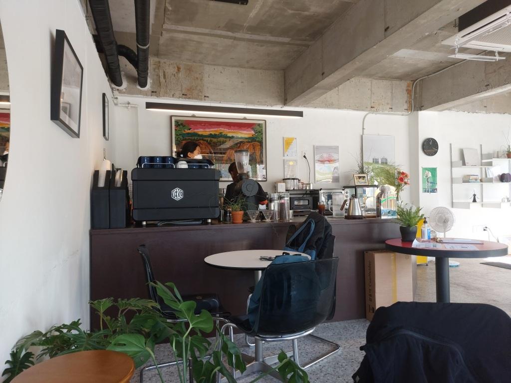 A black espresso machine behind a counter in the corner of the café
