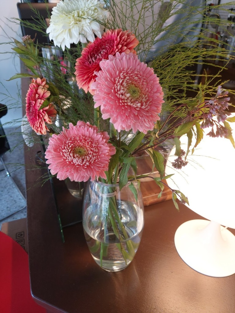 Some pretty pink flowers in a vase on the counter