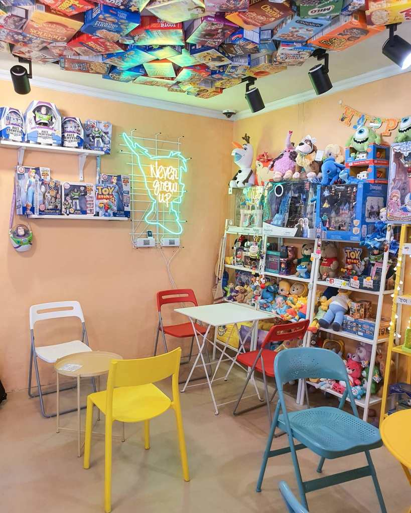 The corner of the cafe with the Peter Pan neon sign and three shelves bursting full of toys and stuffed animals