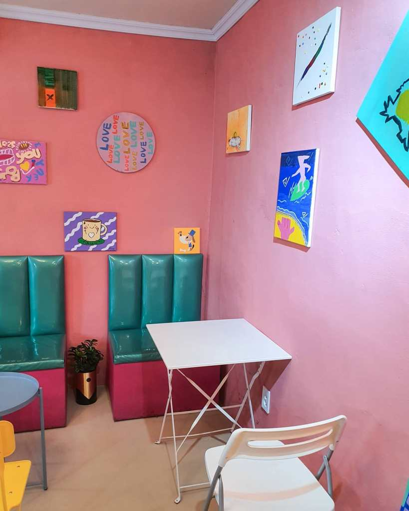 The other seating area, featuring pink walls with fun artwork and teal blue booth seating
